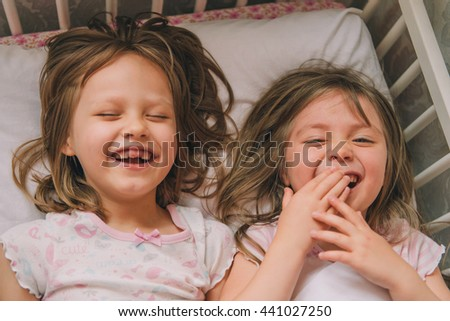 Littlegirl in bed. attractive young girls laugh. two girls dressed in pajamas lying in white bed and laughing.