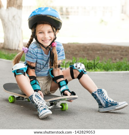 littlesmiling  girl with a helmet sitting on a skateboard