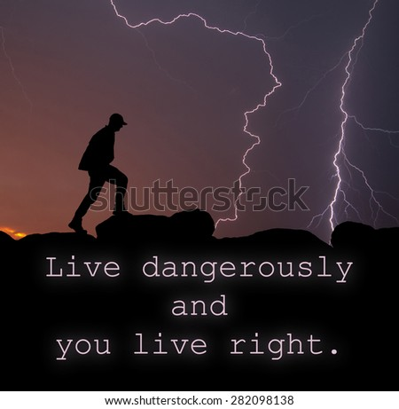 Live dangerously and you live right - quote with a silhouette of a man walking on top of a mountain, with lightning strikes across the sky - stock photo