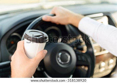 Live life fully. Young pleasant handsome businessman drinking coffee and driving his car while feeling cheerful - stock photo