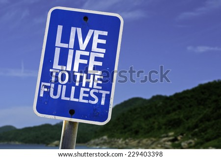 Live Life to the Fullest sign with a beach on background - stock photo