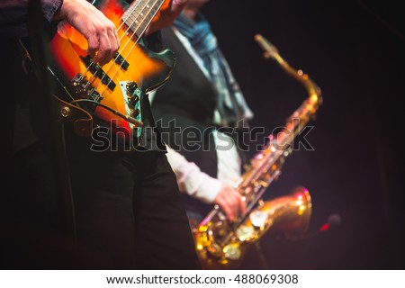 Live music background, guitar player and saxophonist on a stage with colorful illumination, photo with selective focus and retro tonal correction filter effect, old instagram style
