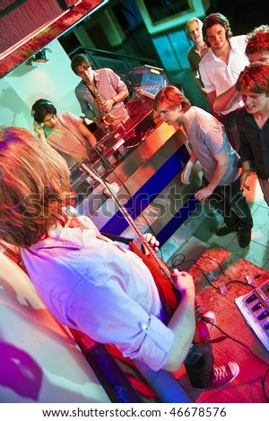 Live performance with DJ, guitarist and saxophonist in a nightclub - stock photo