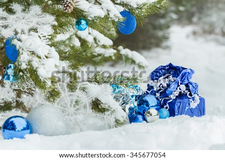 Live snowy pine tree decorated with Christmas ornaments and wrapped presents beneath it on the ground - stock photo