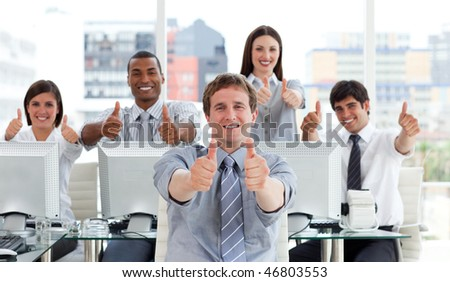 Lively business people with thumbs up in the office - stock photo
