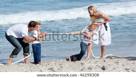 Lively family playing tug of war at the beach - stock photo