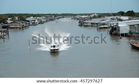 Lively scene on waterway at Mekong Delta, Vietnam. Motor boat move in fast on Ca Mau river, motorboat make wave on water, riverside residential with house make from metal sheet at Camau, Vietnam