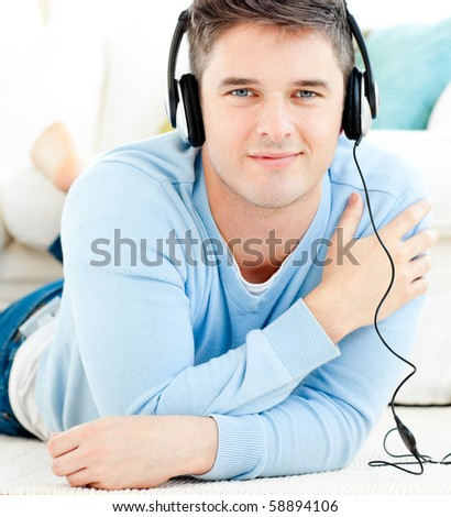 Lively young man listen to music with headphones in the living room - stock photo