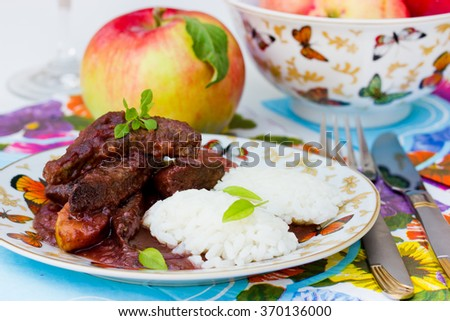 Liver with apples in red wine sauce with rice garnish. Useful and tasty dishes for lunch. Selective focus - stock photo