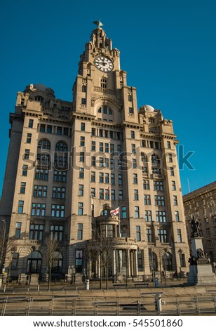 Liverpool Pier Head with the Royal Liver Building, monument and blue sky.