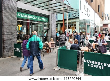 LIVERPOOL, UK - APRIL 20: People sit at Starbucks Coffee on April 20, 2013 in Liverpool, UK. Starbucks is the largest coffee house company in the world, it has 20,891 stores in 62 countries. - stock photo