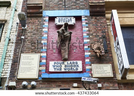 """LIVERPOOL, UK. JUNE 09, 2016: Mural tribute to the Beatles, on Mathew Street, with sign reading """"Four Lads Who Shook The World"""". - stock photo"""