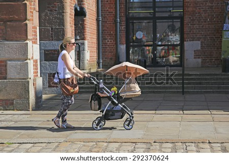 LIVERPOOL, UK - JUNE 30, 2015: Woman pushing her pram, Hartley Quay, Liverpool Bocks. Liverpool is a city in Merseyside, England, on the eastern side of the Mersey Estuary - stock photo