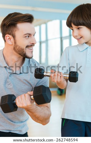 Living a healthy life. Happy father and son exercising with dumbbells while both standing in health club together - stock photo