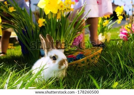 Living Easter bunny with eggs in a basket on a meadow in spring, children in the background - stock photo