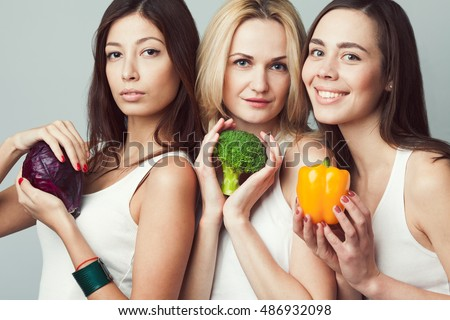 Living food, veggie concept. Portrait of three happy young women wearing white sleeveless shirts, holding vegetables over gray background. Casual clothing. Perfect skin, natural make-up. Studio shot