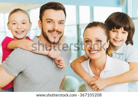 Living healthy life together. Happy sporty family bonding to each other while standing in sports club together - stock photo
