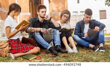 Living in science age. A group of college students sitting on the grass and preparing for the test.