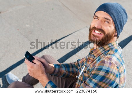 Living in the digital world. Top view of handsome young man sitting and writing a message  - stock photo