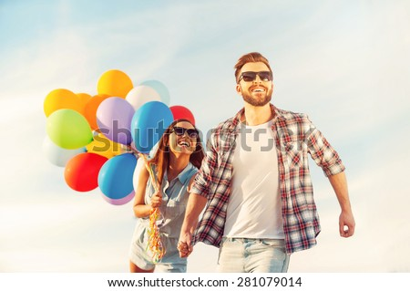 Living life to the fullest. Cheerful young couple holding hands and smiling while walking outdoors with colorful balloons - stock photo