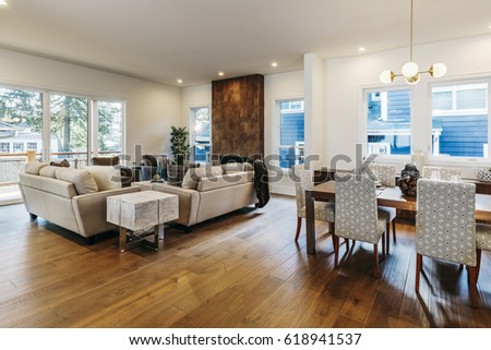 Living room and dinning room of new modern home with wood flooring and lights on.