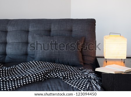 Living room detail.  Cozy gray sofa with cushion and throw, table lamp and book. - stock photo