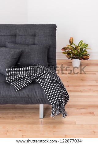 Living room detail. Gray sofa with cushions and throw, and colorful plant. - stock photo