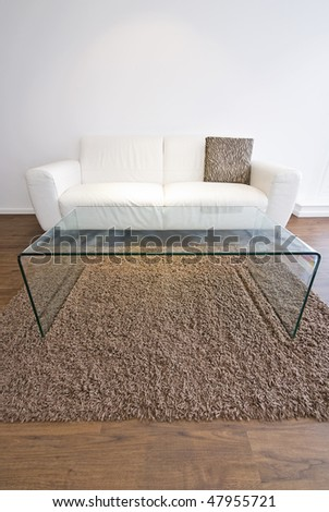 Living room detail with white leather sofa and designer glass coffee table - stock photo
