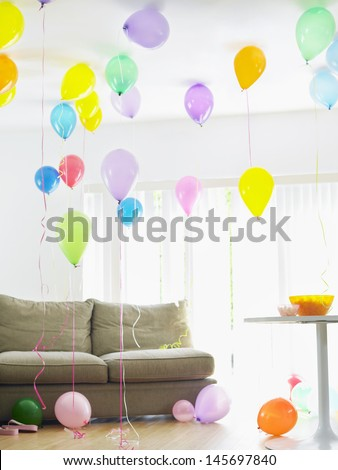 Living room full of colorful balloons by sofa - stock photo