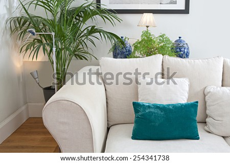 Living room home interior with a white sofa, with wooden floors and decorative vases, house interior. Comfortable living lifestyle. Elegant home space with textures and design elements, indoors. - stock photo