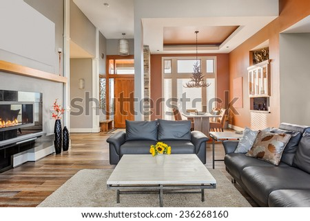 Living Room in Luxury Home with Fireplace, Coffee Table, and Hardwood Floors - stock photo