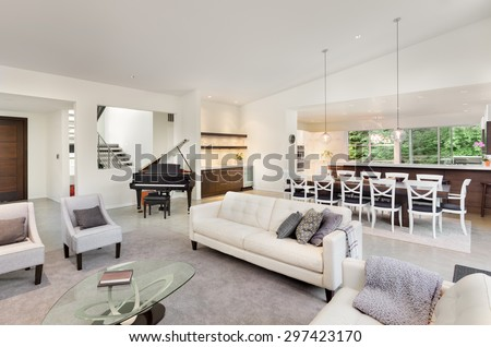 Living Room in Luxury Home with Wide Open Floor Plan, View of Kitchen, Piano, Entry, Wet Bar, Dining Table - stock photo