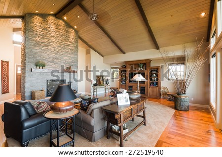 Living Room in New House:Large Furnished Living Room with Fireplace, Vaulted Ceiling, Entertainment Center, Television, Couch, Coffee Table, and Rug - stock photo