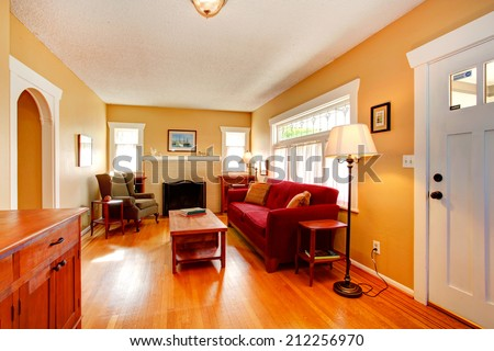 Living room in soft ivory with cozy fireplace and red couch - stock photo