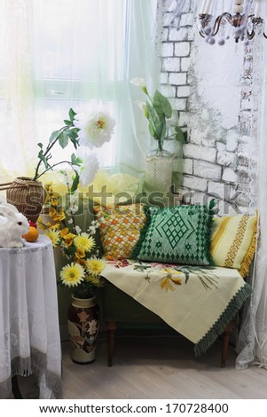 living room interior corner with colored pillows, vases and flowers  - stock photo