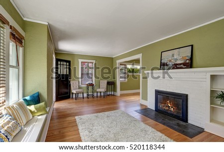 Living room interior design of craftsman home with white brick fireplace, built-in shelves, window seat with pillows, pale green walls and hardwood floor. Northwest, USA