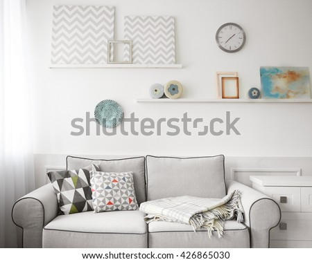 Living room interior, grey couch and shelves with paintings on wall background - stock photo