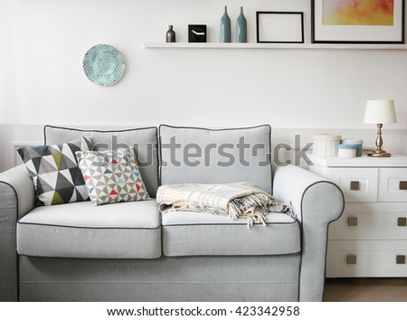 Living room interior, grey couch and shelves with paintings on white wall background