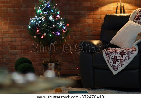 Living room interior with black armchair and Christmas tree on brick wall background - stock photo