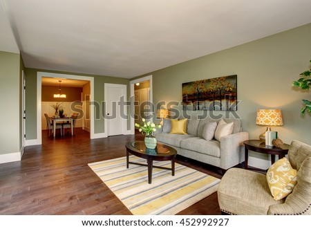 Living room interior with green walls hardwood floor and rug. Dining area