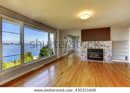 Living room interior with hardwood floor, fireplace with natural stone tile and water view - stock photo