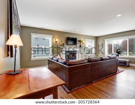 Living room interior with hardwood floor. View of burgundy leather couch and cozy fireplace with tv above it
