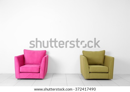 Living room interior with pink and green armchairs on white wall background - stock photo