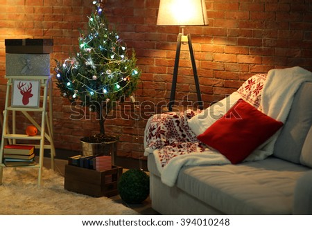 Living room interior with sofa, lamp and Christmas tree on brick wall background - stock photo