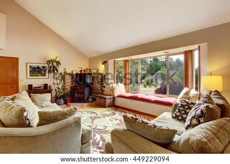 Living room interior with vaulted ceiling and cozy sitting place with red pillows. Also fireplace in the corner decorated with brick wall and pots with plants.