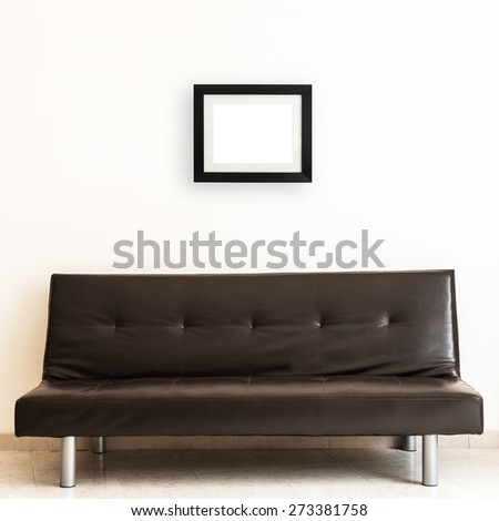 Living room with blank picture frame over a dark sofa. Rectangular basic frame. - stock photo