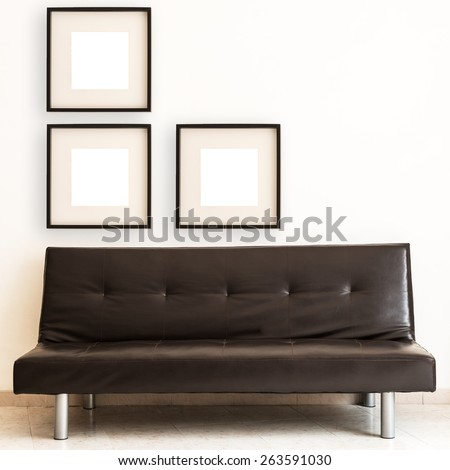 Living room with blank picture frame over a dark sofa. Squared frame. - stock photo
