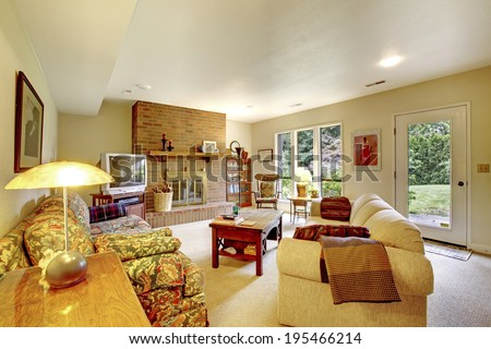 Living room with brick background fireplace, floral and plain sofas, rustic coffee table and TV. Room has exit to backyard deck