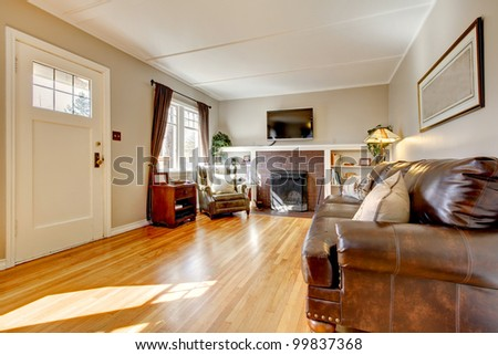 Living room with brown curtain and hardwood floor and leather sofa. - stock photo