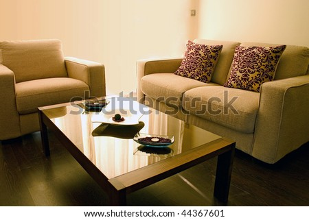 Living room with cosy sofa and arm chair and small table. - stock photo